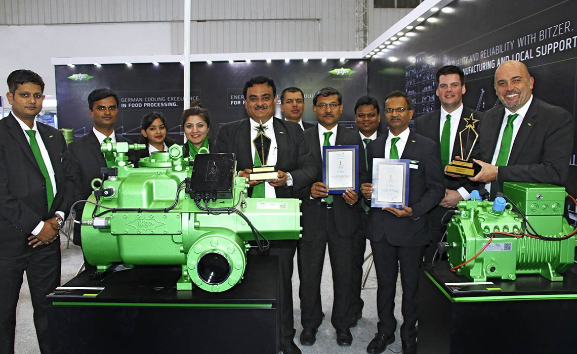 BITZER representatives stand together with the two ACREX prices behind BITZER compressors