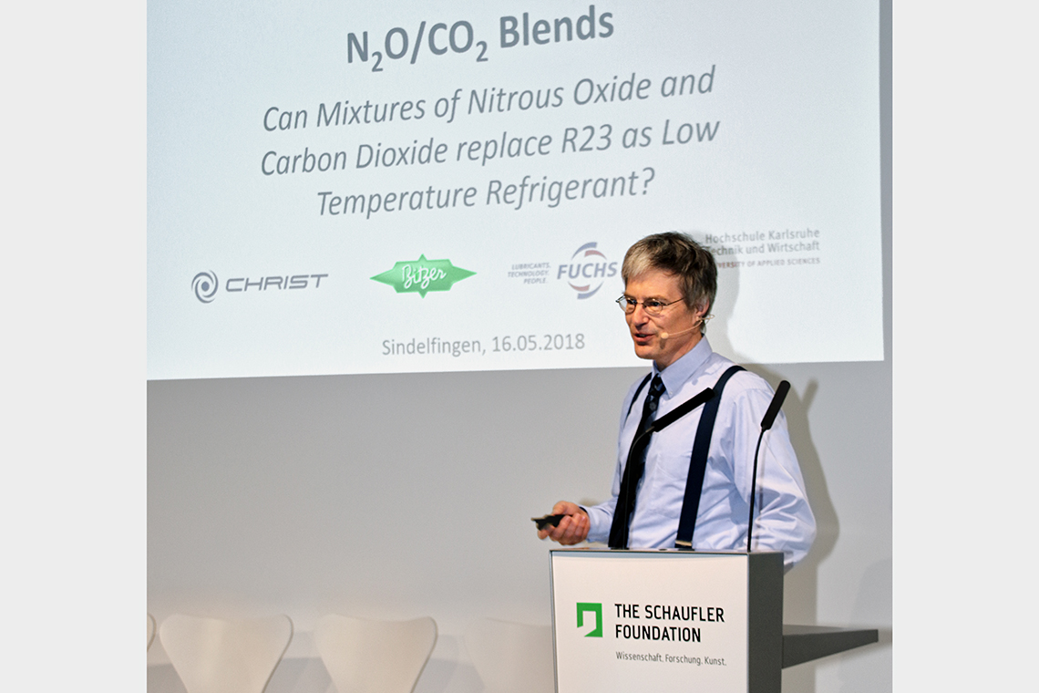 Prof. Dr. Michael Kauffeld, Speaker of the Institute of Refrigeration, Air-Conditioning, and Environmental Technology at Karlsruhe University of Applied Sciences, stands during the international Art of Compression symposium on the podium