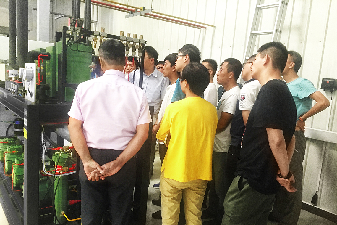 Chinese people stand around BITZER reciprocating compressors and take a look at the refrigeration system