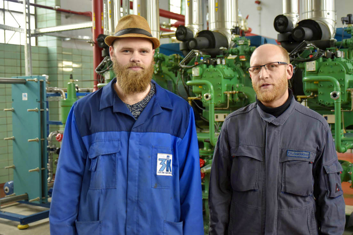 Moritz Kruse (l.), planner and project manager at 3K, and Christoph Beidecker, technical manager at the Bochum meat trade, in front of the BITZER compressors in the EC slaughterhouse in Bochum