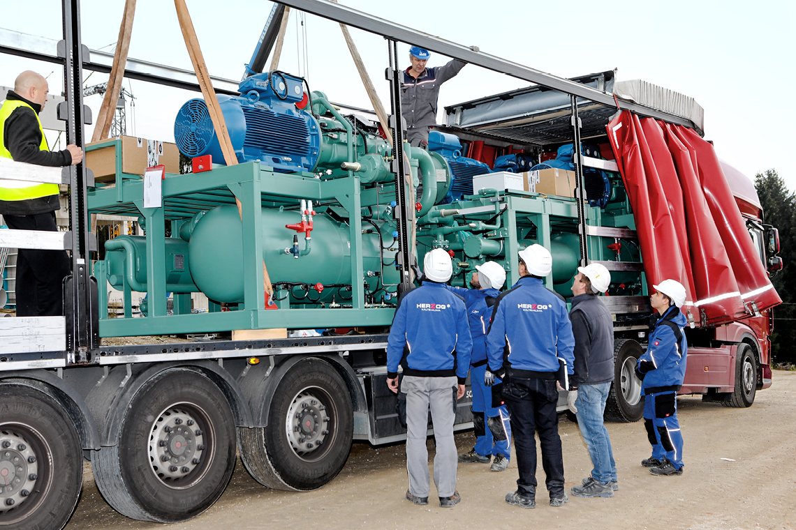 Lorry with BITZER ammonia compressor packs in the background and installers towards the front