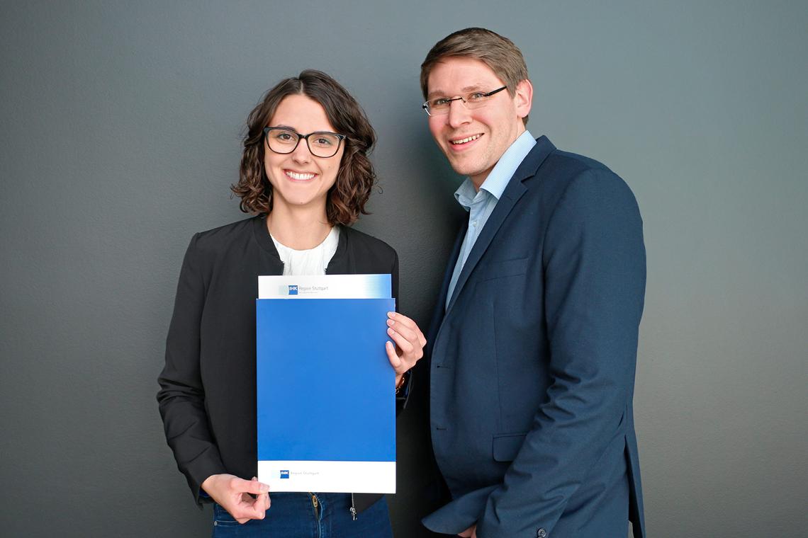 Maren Weippert und Tobias Baisch von BITZER stehen vor grauem Hintergrund und halten Urkunde hoch