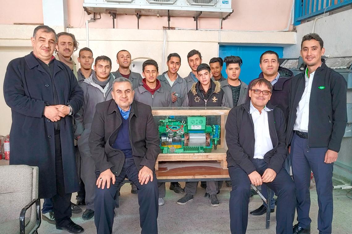 Studenten des Wadi Al-Seer College in Amman und BITZER Mitarbeiter mit Hubkolbenverdichter-Schnittmodell von BITZER