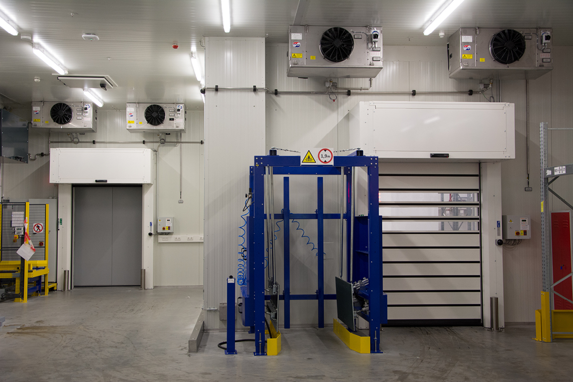 Evaporator plant in a production hall with fans on the ceiling and blue steel construction in the middle