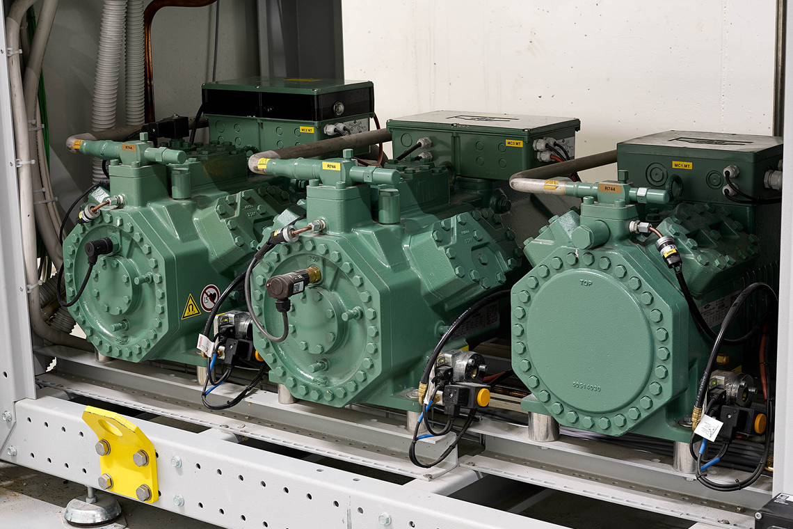 Detail photo: Green BITZER reciprocating compressors and IQ modules in metal frame