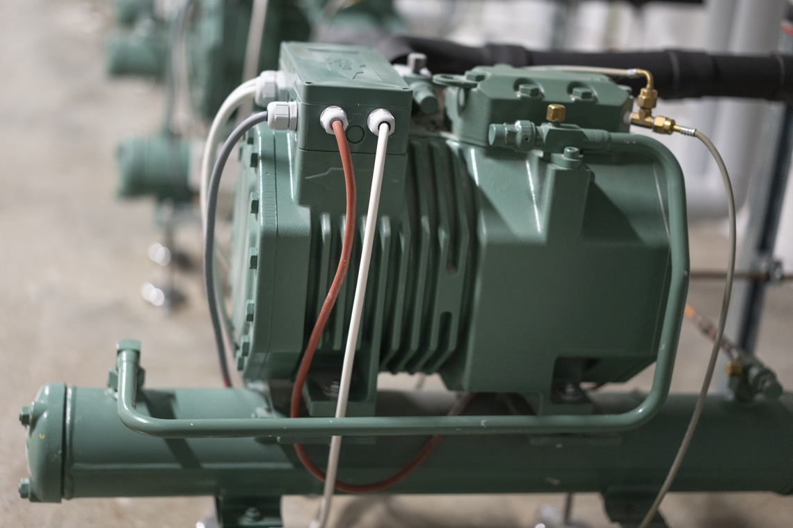 Detail photo: Green BITZER ECOLINE compressor and a condenser from the BITZER K-series